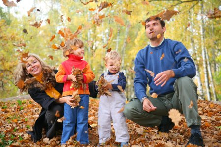 Photo for Family of four throw autumnal leaves - Royalty Free Image