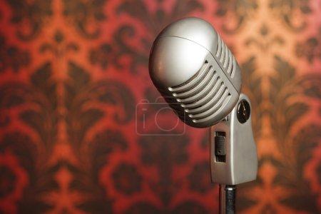 Photo pour Microphone métal vintage sur un stand photographié sur fond de papier peint d'ornement jaune-rouge - image libre de droit