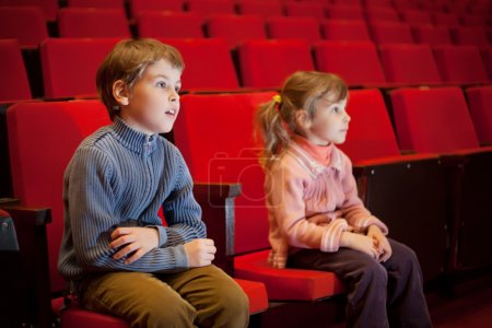 Boy and little girl sitting on armchairs at cinema