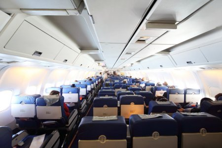 Airplane cabin with passengers general view