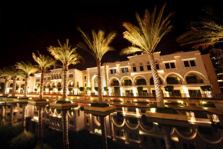 Night Dubai street with palms and pool, United Arab Emirates
