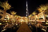 Burj Dubai, night Dubai street with palms and pool general view,