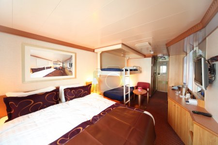 Ship cabin with big double bed and two children beds general vie