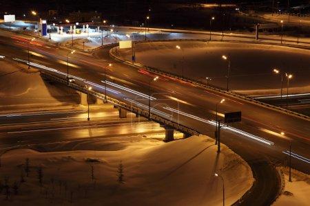Photo pour Paysage urbain hivernal nocturne avec grand échangeur, colonnes d'éclairage et pont - image libre de droit