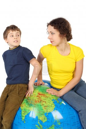 Mother and son sitting on big inflatable globe and looking to ea