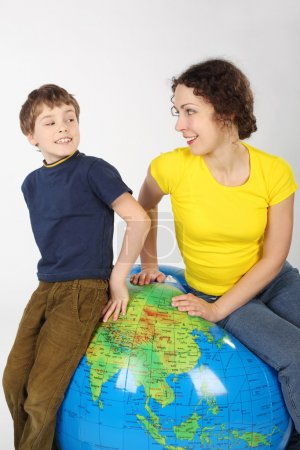 Mother and son sitting on big inflatable globe, smiling and look