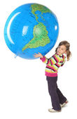Little girl standing and holding big inflatable globe over her h