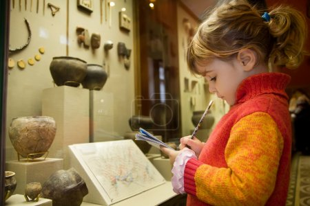 Little girl writes to writing-books at excursion in historical m