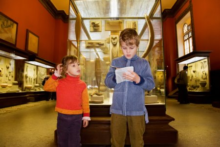 Boy and little girl at excursion in historical museum near exhib