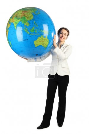 Photo for Young woman in white jacket standing and holding for two hands big inflatable globe, isolated on white - Royalty Free Image