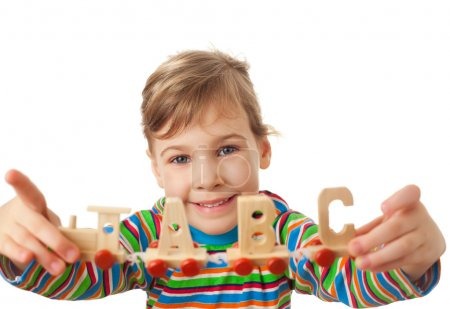 Photo for Pretty little girl keeps in hands toy wooden steam locomotive with cars in form of alphabet letters isolated on white background - Royalty Free Image