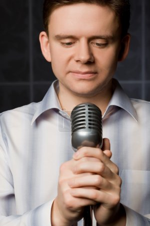 Young man in shirt keeps in hands microphone