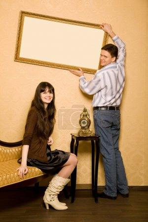 Woman sitting on sofa in room and smiling man hang up on wall picture