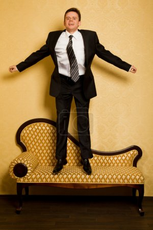 Cheerful businessman in suit jumping on sofa in room