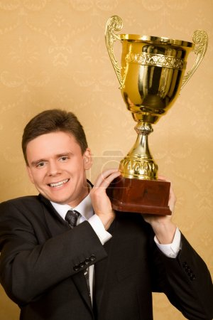 Smiling businessman in suit with win cup in hand