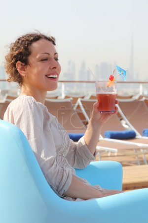 Beauty woman sitting in blue armchair on cruise liner deck and h