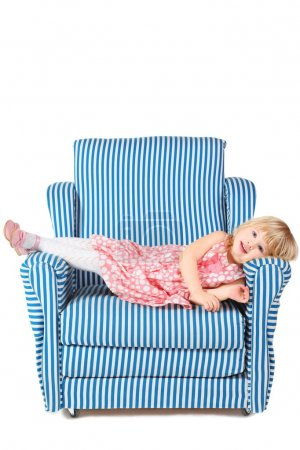 Photo pour Petite fille portant robe et chaussures est couché sur un fauteuil confortable. isolé. - image libre de droit