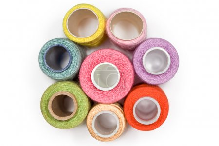 Spools with multi-coloured sewing threads isolated...