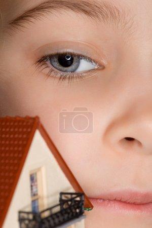 Photo pour Visage de petite fille près de la maison en plastique de jouet avec balcon - image libre de droit