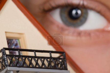 Photo pour Fragment de visage de personne près de la maison en plastique de jouet avec balcon, près des yeux vers le haut - image libre de droit