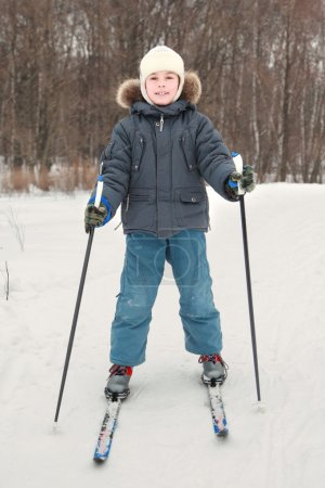 Little boy in warm sport dress skiing at forest, full body, look