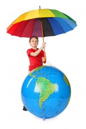 Boy in red shirt with multicolored umbrella and inflatable globe