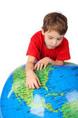 Boy in red shirt leans on inflatable globe isolated on white bac
