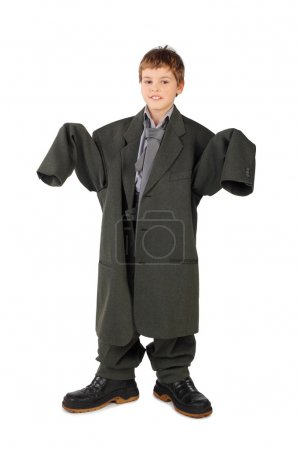 Little boy in big grey man's suit and boots standing isolated on