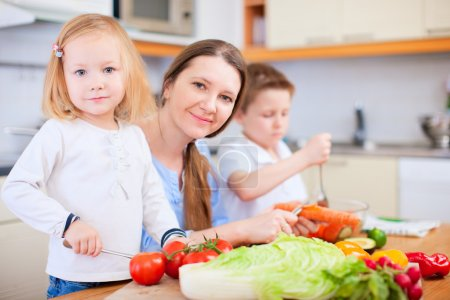 Photo for Young mother and her two kids making vegetable salad - Royalty Free Image