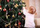 Malá dívka zdobení vánoční strom