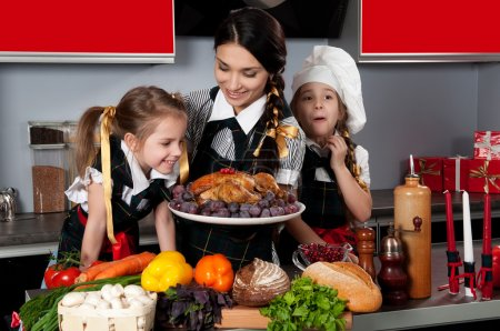 Photo for Mother with two daughters in the kitchen preparing Christmas dinner with turkey and vegetables - Royalty Free Image