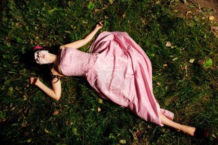 Photo pour Fille de mensonge sur l'herbe comme un cadavre, peuvent être utilisés pour le concept de la poupée cassée - image libre de droit