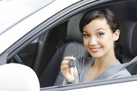 Photo pour Jolie fille dans une voiture montrant la clé - image libre de droit