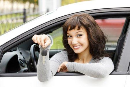 Photo pour Jolie conductrice dans une voiture blanche montrant la clé de la voiture - image libre de droit