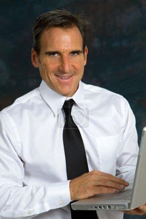 Photo pour Heureux homme d'affaires mature souriant, portant une chemise blanche et une cravate, tient un ordinateur portable et sourit . - image libre de droit