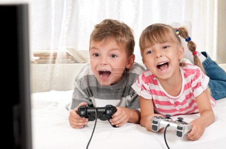 Photo for Happy children - girl and boy playing a video game - Royalty Free Image