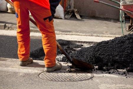 Photo pour Travailleurs de l'asphalte dans la rue - image libre de droit