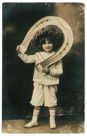 Photo for RUSSIA - CIRCA 1906: Retro postcard with weathered edges on white background printed in circa 1906, Russia. Vintage hand-tinted photograph depicts a young boy w - Royalty Free Image
