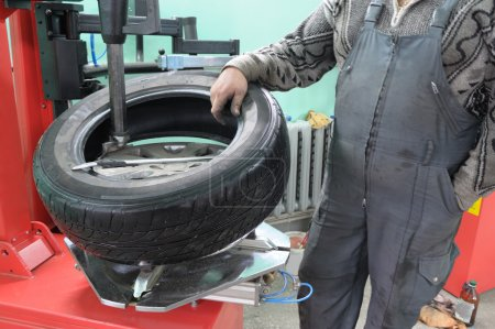 Photo for The car mechanician changes a tyre cover on an automobile wheel. - Royalty Free Image