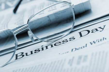 Eyeglasses lie on the newspaper with title Business day. Blue to