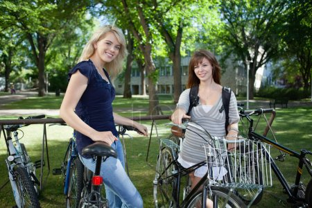 Girls standing with bicycle