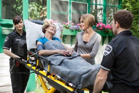 Photo pour Femme senior avec membre de la famille à côté étant transportée à l'hôpital - image libre de droit
