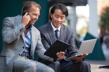 Photo pour Les hommes d'affaires utilisant ordinateur portable et tablette PC pendant la communication sur téléphone portable - image libre de droit