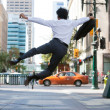 Rear view of business man jumping in air and kicki...