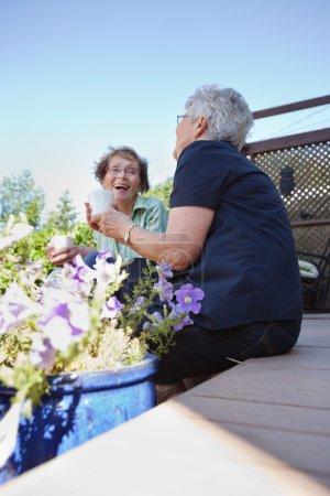 Photo pour Deux femmes âgées à l'arrière cour de boire des boissons chaudes et de rire ensemble - image libre de droit