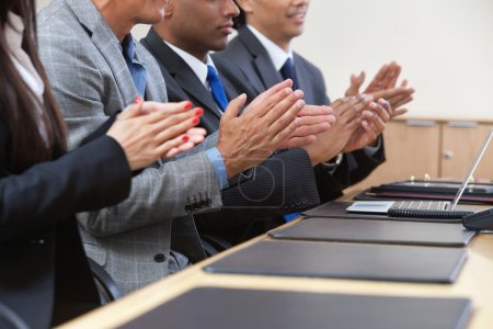 Photo for Businesspeople sitting in a row and applauding - Royalty Free Image