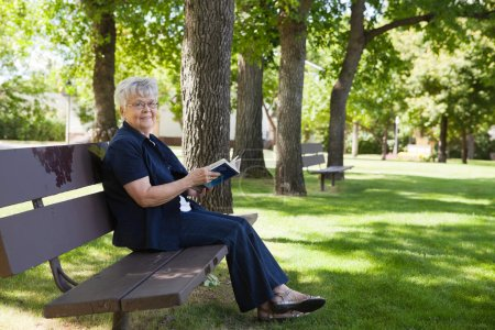 Photo for Portrait of senior woman sitting on a park bench reading a book - Royalty Free Image