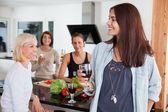 Female friends enjoying drink in kitchen