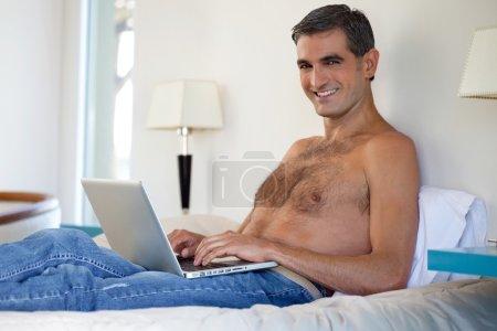 Shirtless Man Working on Laptop