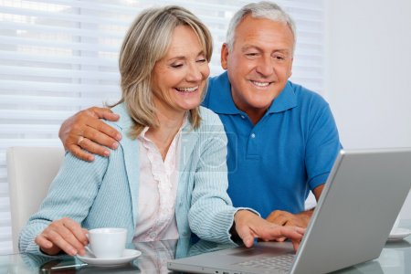Photo for Mature woman having tea and browsing internet with her husband on laptop - Royalty Free Image
